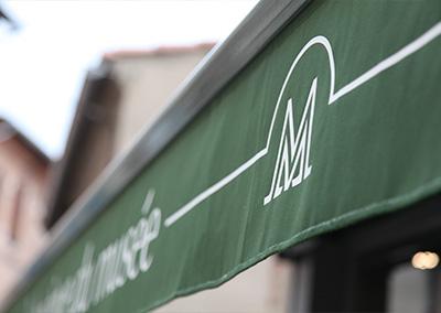 Gros plan sur la marquage du logo du Musée de la Mode sur tissus, devanture de la boutique à Albi