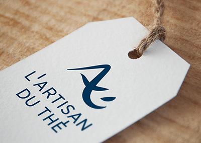 Impression du logo de l'Artisan du Thé, boutique de vente en ligne de thé sur une étiquette en papier texturé.